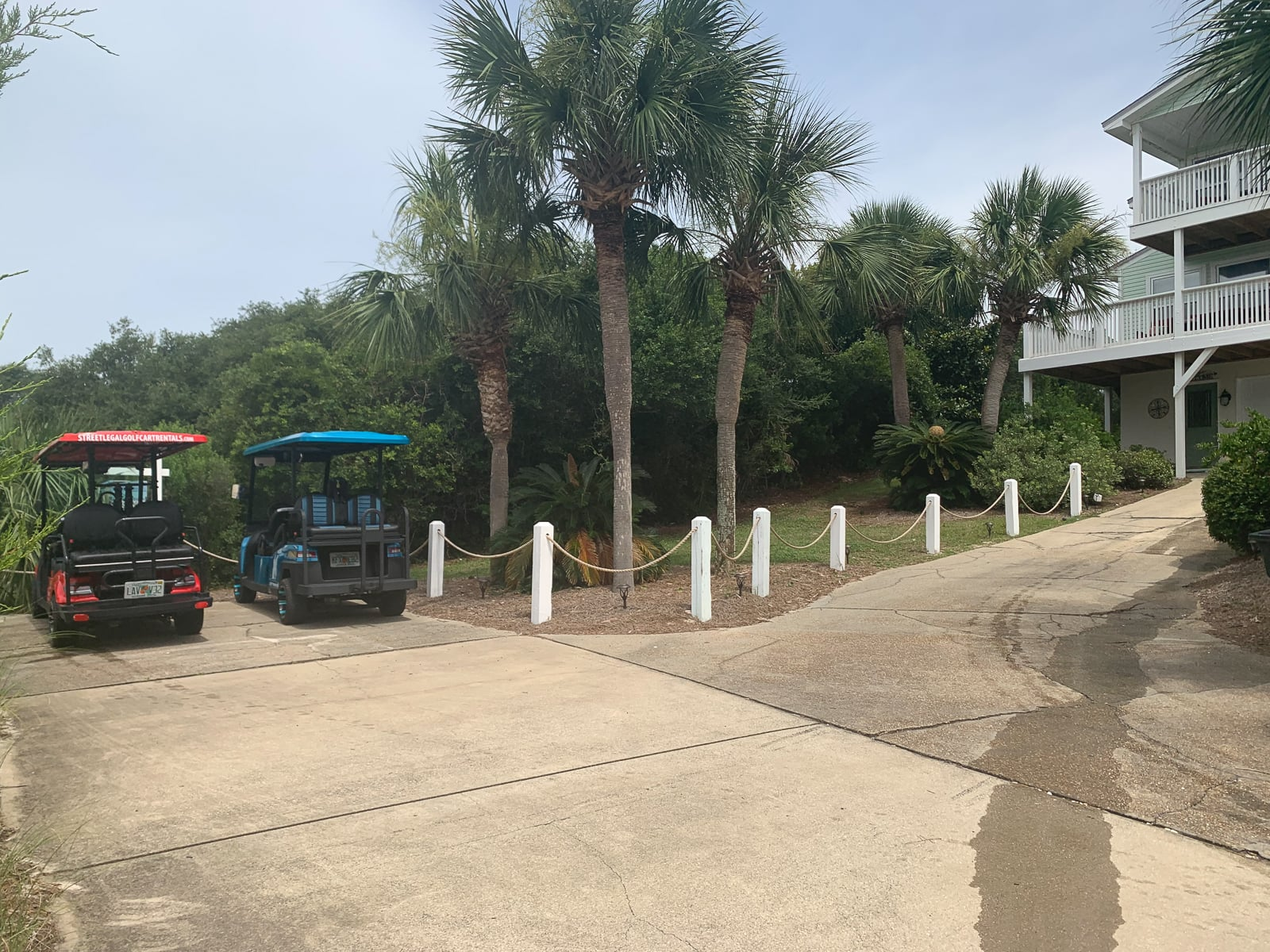 two golf carts parked at an Inlet Beach driveway